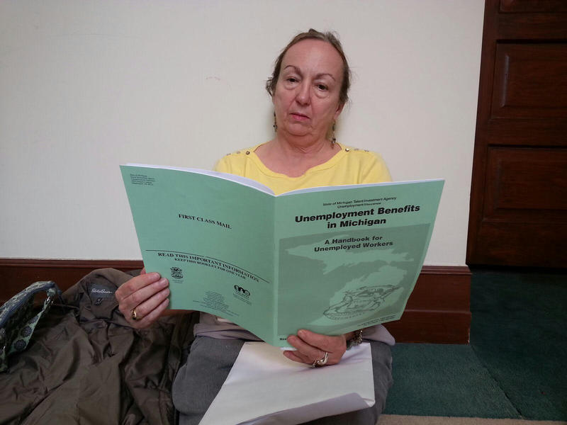 Charisse Nilles reads an unemployment booklet after being laid-off from EMU.