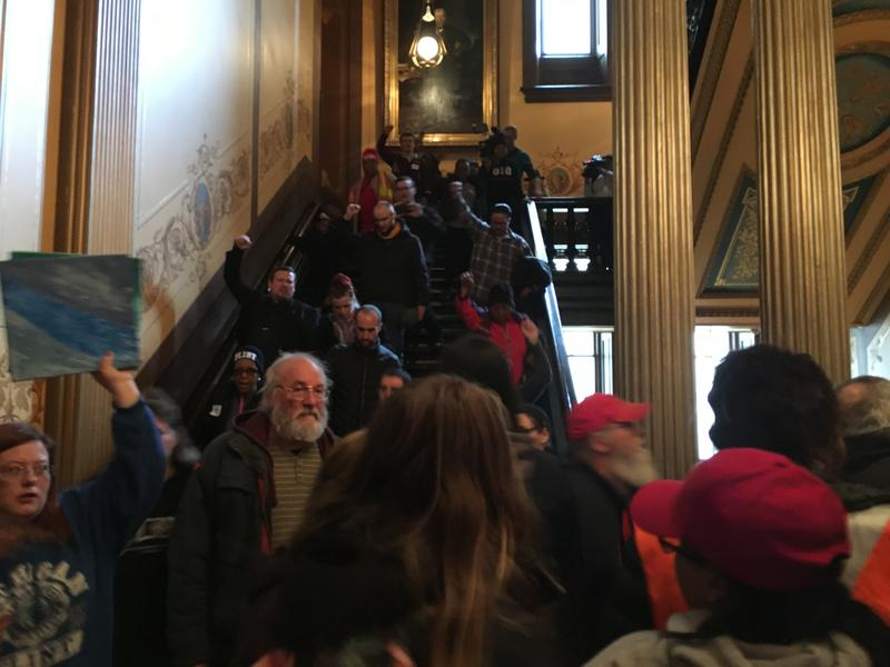 Protestors march down steps inside the state Capitol after interrupting a state House of Representatives session.
