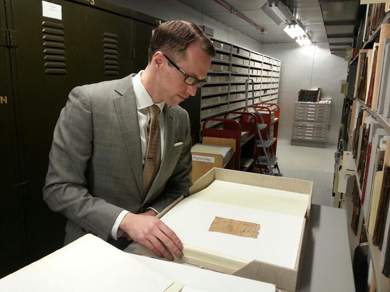 Archivist Brendan Haug reading text on a papyrus.