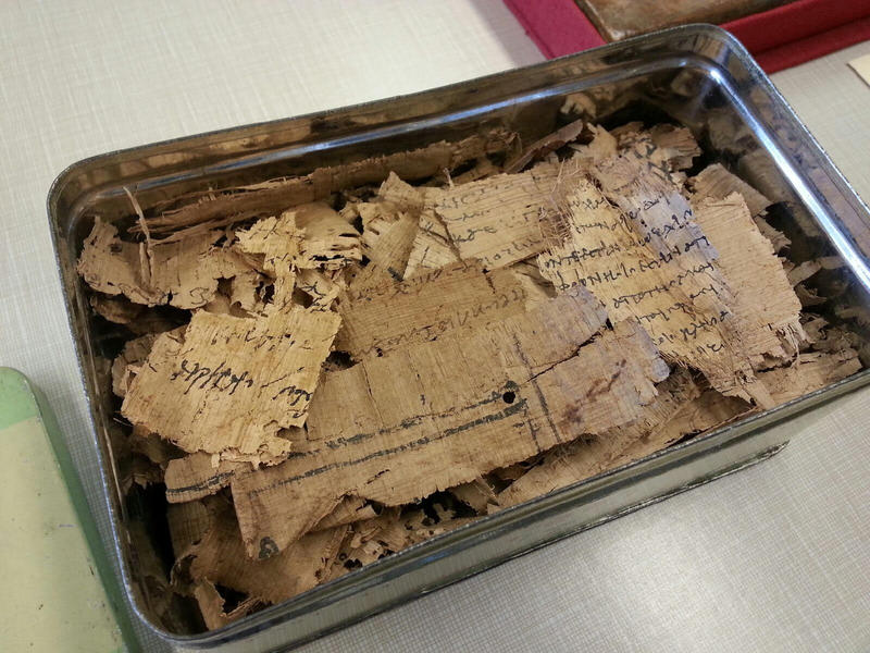 Pieces of papyri in a tin can.