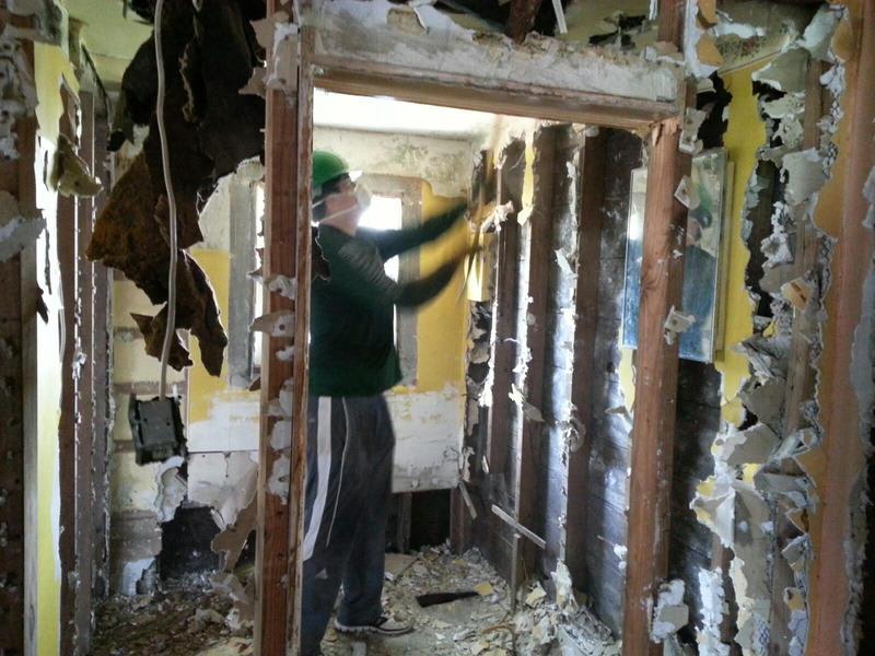 "Offensive Lineman Michael ""Big Mike"" Van Hoeven demolishing a bathroom ceiling."