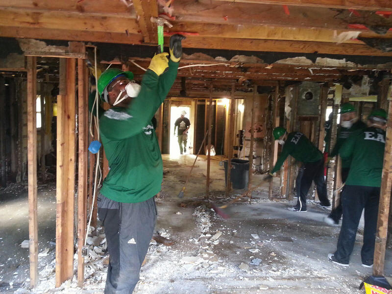 EMU football players demolishing a house in Ypsilanti Township.