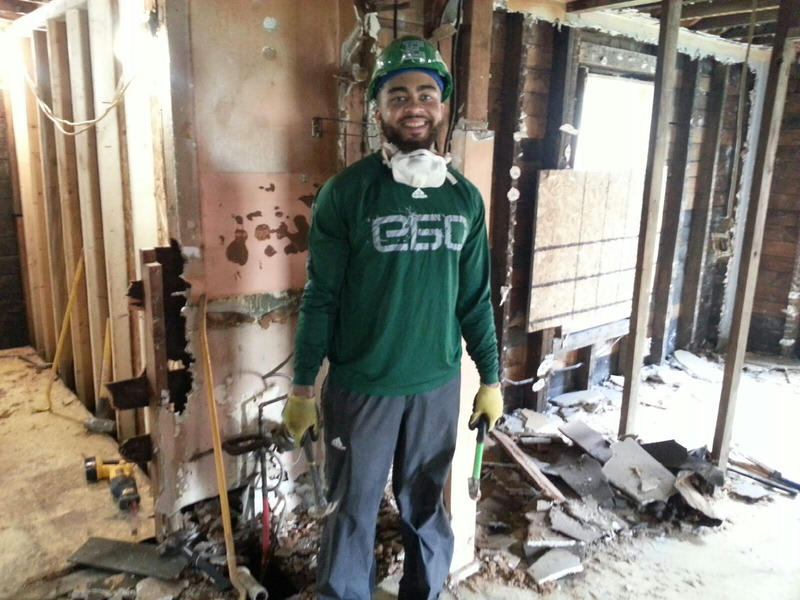 Eagles player Ikie Calderon gets ready to pull nails off the wall.
