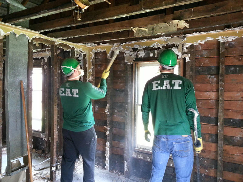 EMU football players remove nails and drywall from the house.