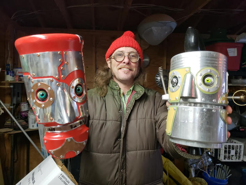 Artist Cre Fuller holds up two of his robot creations.