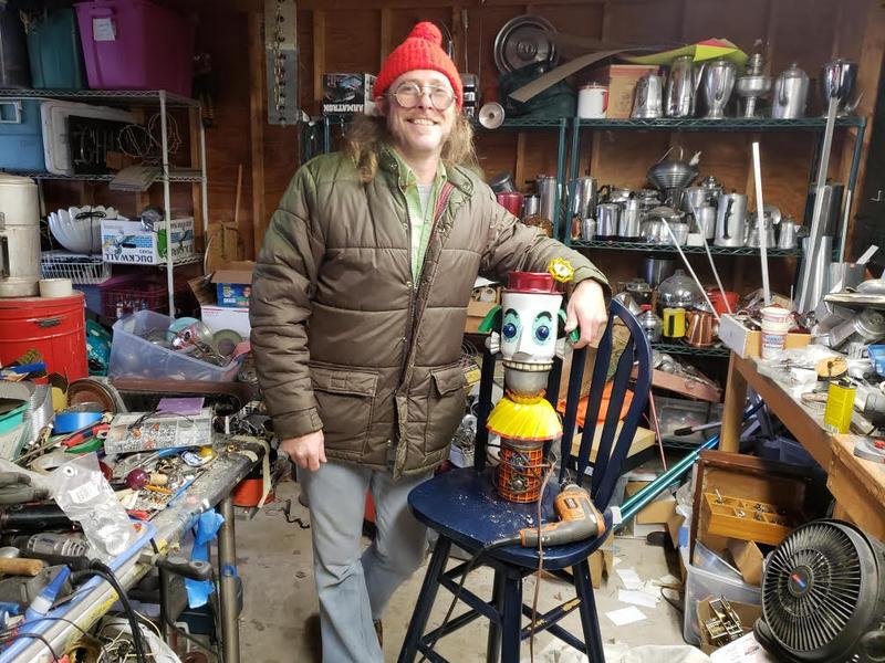 Cre Fuller stands next to a clown robot lamp.