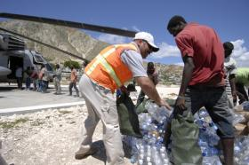 Relief workers unload bottles of water in Gonaives, Haiti. Find out what it takes to be a humanitarian aid worker.