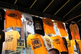 A Strip District vendor sells Pittsburgh Steelers t-shirts on the roadside.
