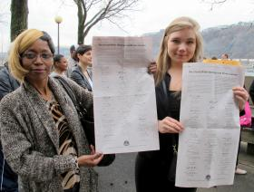 Rivers Casino employees Lisa Washington and Brittany Swiger hold up copies of a letter of support signed by community leaders and lawmakers.