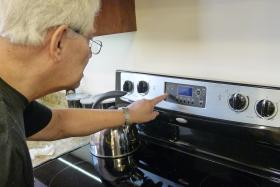 Ron Dambrosia sets the timer on the oven in MyHome.