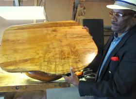 Earl Johnson shows a completed coffee table.