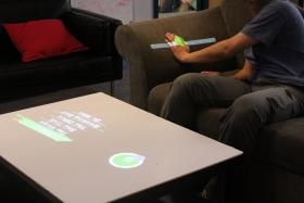 WorldKit allows users to turn any surface into a touch screen, so a couch arm can be used as a remote control.