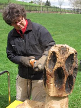 Janise Crow puts finishing touches on a morel mushroom made from Homewood Cemetery wood.