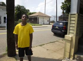 Isaiah Thompson, 13, stands in front of the Allegheny Youth Development offices.