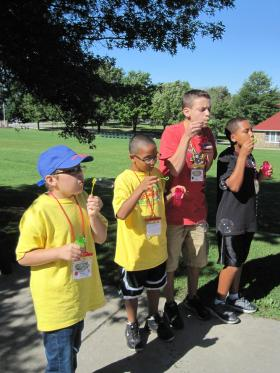 Kids at Camp Huff & Puff exercise their lungs by blowing bubbles.