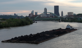 A barge pulls coal along the Monongahela River.