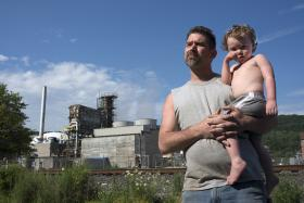 Rob Sickles with his son Spencer, 3, on the street between his home and the Dyno Nobel plant in Donora.