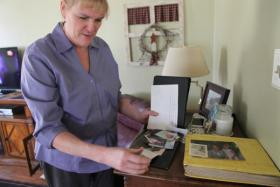Norma shuffles through family photos of her mother, whom she has been unable to see since last Christmas.