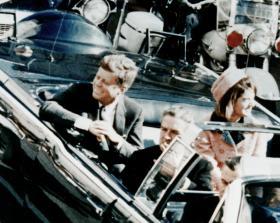 President Kennedy riding in a motorcade through Dallas, TX before being shot.