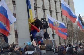 Pro-Russian protesters remove a Ukrainian flag and replace it with a Russian flag in front of a State Administration building near Mariupol, Ukraine