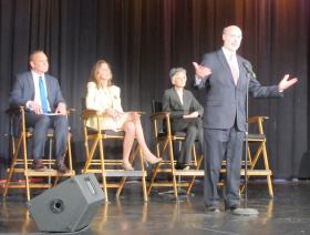 Tom Wolf stands at the mic Tuesday night at a debate featuring all four Democratic gubernatorial candidates. (L-R) Rob McCord, Katie McGinty and Allyson Schwartz wait their turn to speak.