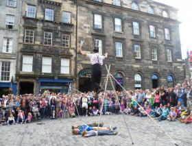 A French circus performer advertises an upcoming fringe show in Edinburgh, Scotland.