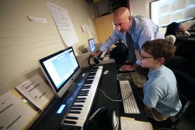 Pittsburgh Science and Technology Academy teacher Matt Ferrante works with sixth grader Hunter Bash during a recent school day. Ferrante, who teaches music technology, said unlike some other schools where he's taught, he never feels peripheral at SciTech.