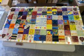 The 7-by-4 foot ceramic tile quilt calls attention to violence against women.