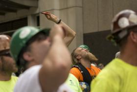 Workers look up and snap photos as the last steel beam is lifted to the top of the Tower at PNC Plaza on Tuesday.
