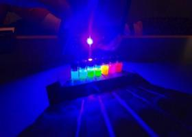 Graduate student Lauren Powell shines a blue LED through vials of Quantum Dots, manufactured by Pittsburgh-based Crystalplex. Each vial contains trillions of nanoparticles.