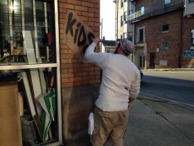 """A member of the """"Southpaw"""" crew applies """"graffiti"""" to a building along Brownsville Road."""