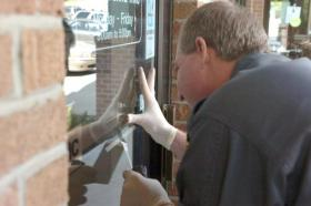 Pennsylvania State Police Trooper Richard Hunter tries to lift a fingerprint from the front door of Community Bank in Cecil Township, Washington County, shortly after the bank was robbed in July 2009.