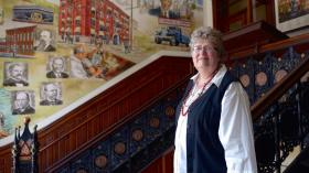 Joann Wheeler stands in the lobby of the National Transit Building. The lobby mural depicts big players of the oil industry, like John D. Rockefeller.
