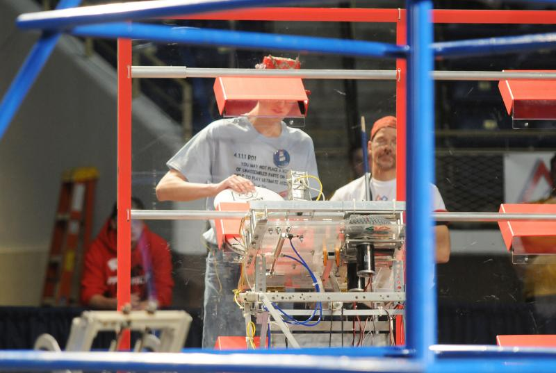Frisbees are loaded into a robot during a practice run.