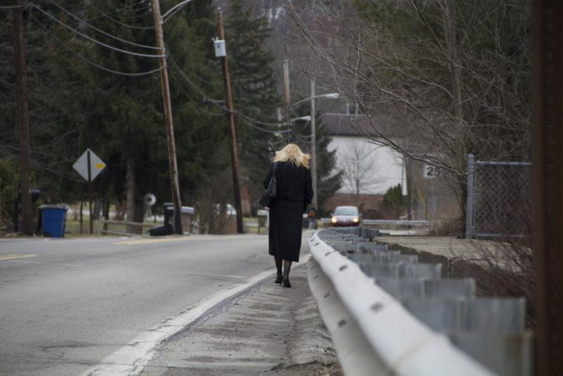 A commuter walks home from Monroe T Station along Brightwood Rd.