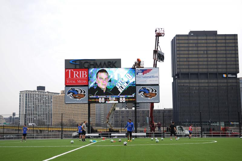 Workers install a Highmark Stadium sign as Pittsburgh Riverhounds players practice below.