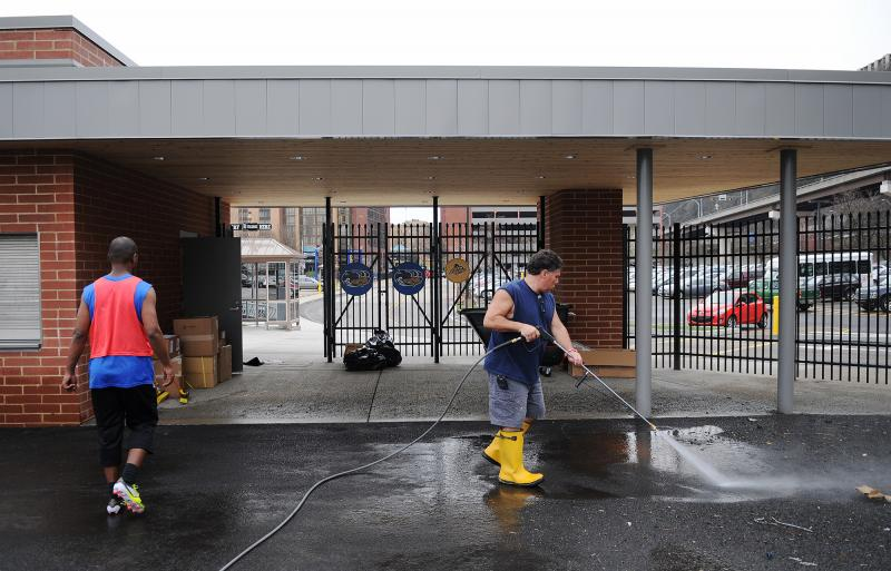 John McGrath (right) facility manager at Highmark Stadium, uses a power washer as the Highmark Stadium grounds are readied.