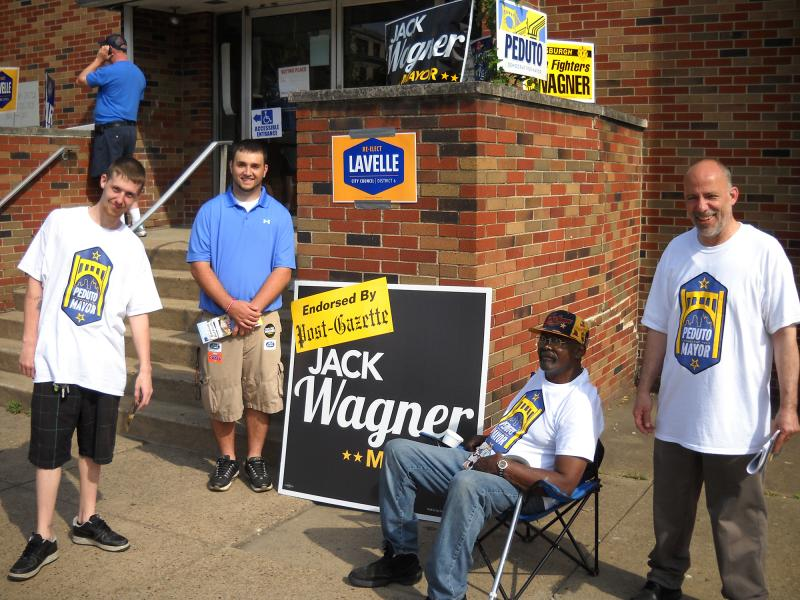 Jack Wagner supporter Colman Mazur (in blue, facing camera) is surrounded by Bill Peduto backers at a polling place on East North Street.