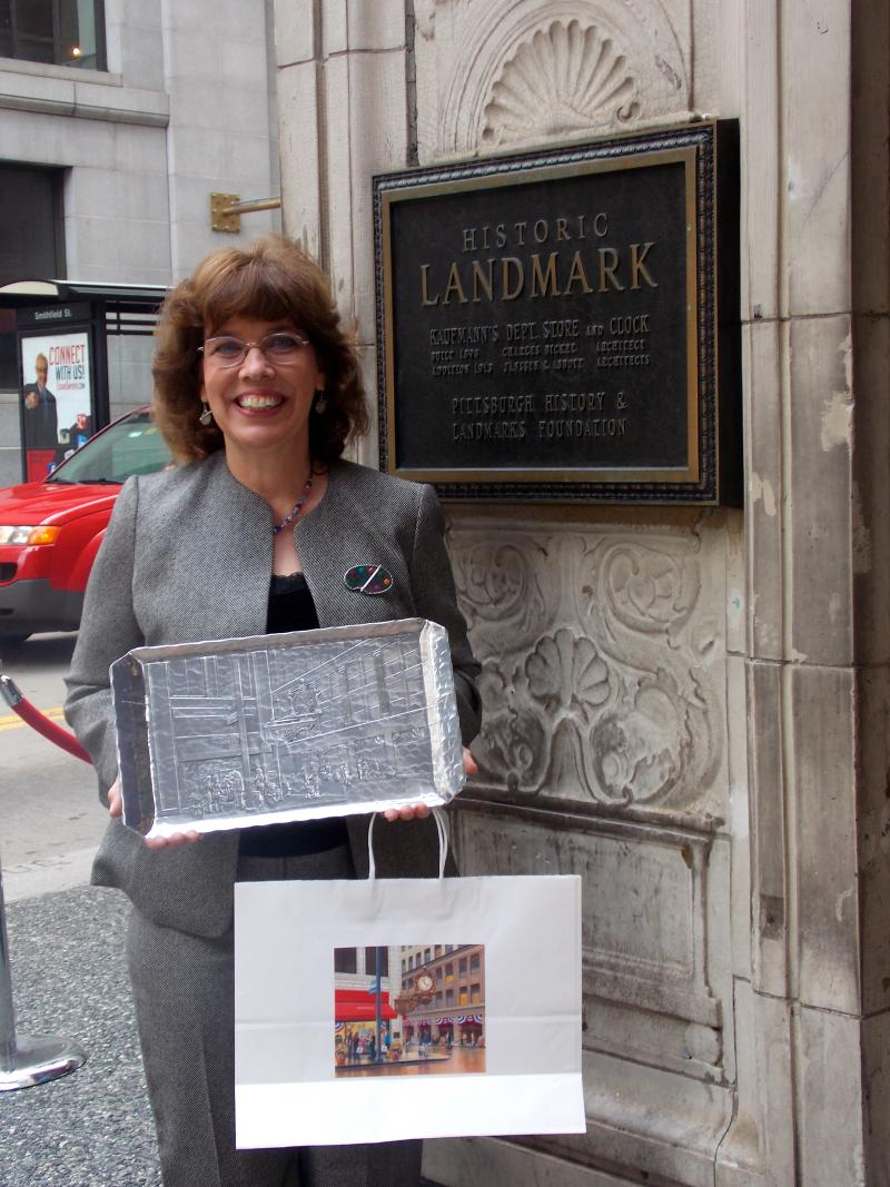 Barnicott stands beside the plaque designating the Kaufmann's Clock as a Pittsburgh Historical Landmark