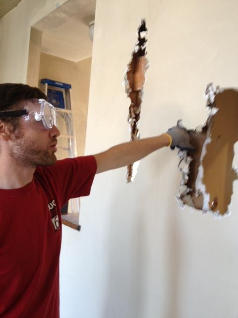 Andy carefully hammers and pulls out drywall