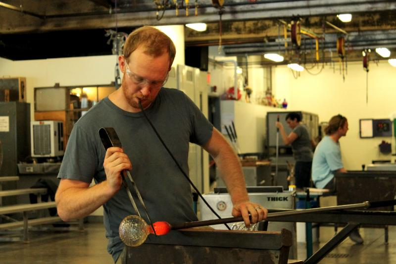 Glass work requires some skillful multi-tasking as Jason Fork blows, rotates and shapes the molten glass into the shape of a cup.