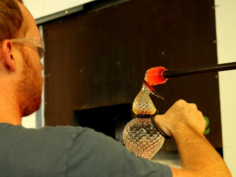An assisting artist helps attach a smaller piece of molten glass to form the base of the cup.