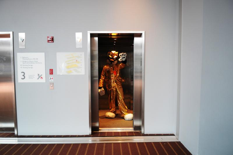 A fursuiter waves goodbye as elevator doors shut. The convention ended Sunday.