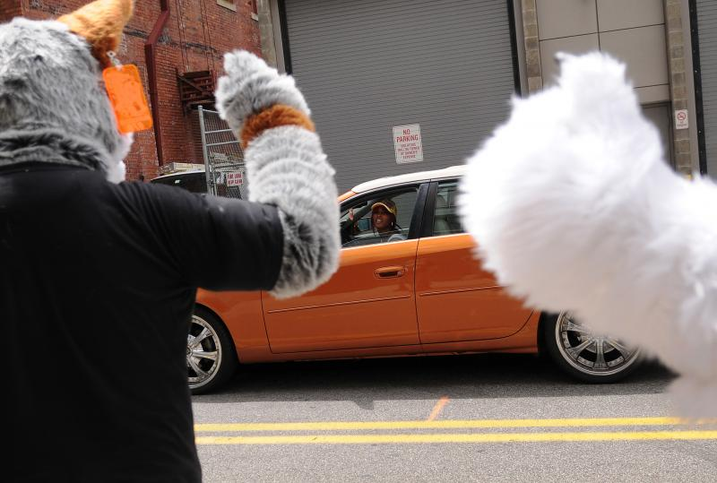 A passing driver yells hello to a group of furries walking in downtown Pittsburgh on Friday.