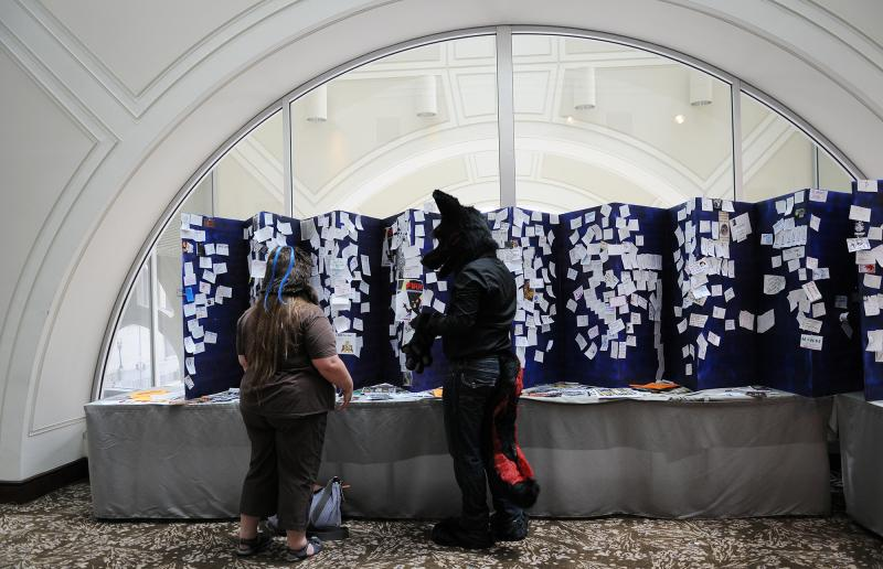 Convention-goers check a message board on Friday. Throughout Anthrocon, furries post notes advertising parties, ways to get in touch and other messages.