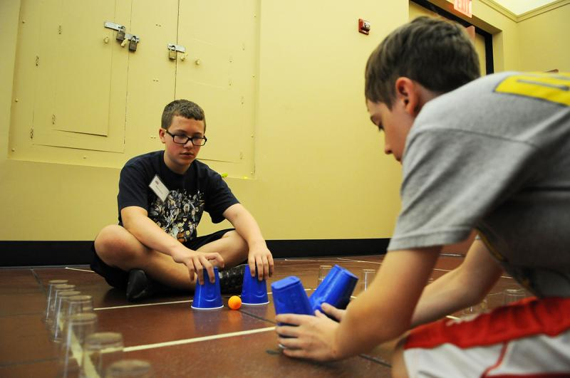 Max O'Malley, 12, (left) and Dan Helmeci, 12, play a game using ping pong balls and plastic cups. Max and his group created the game, called Alley Ball Squared, based on the concept of air hockey.