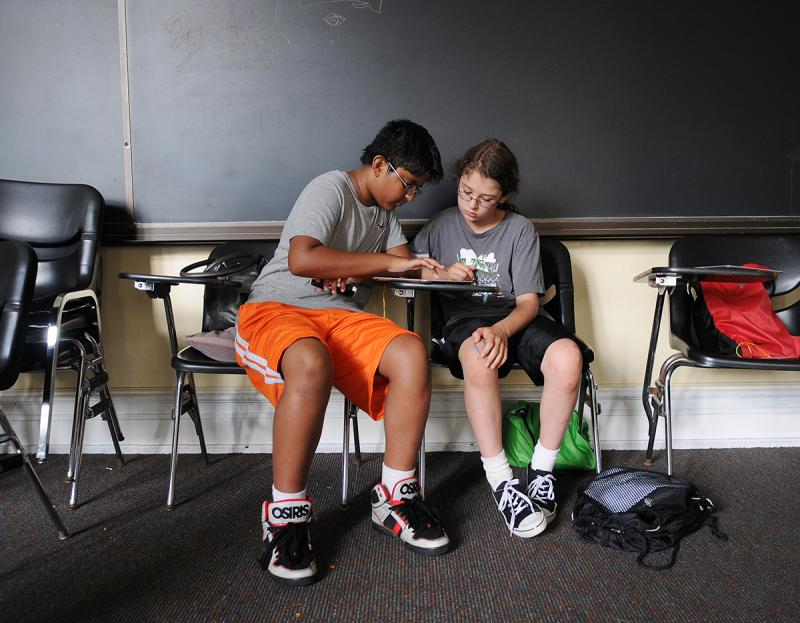 Vineeth Sharma, 12, (left) and Ceu Gomez-Faulk, 11, use an iPad to make a trailer for a movie about a planet they're designing as part of the camp.
