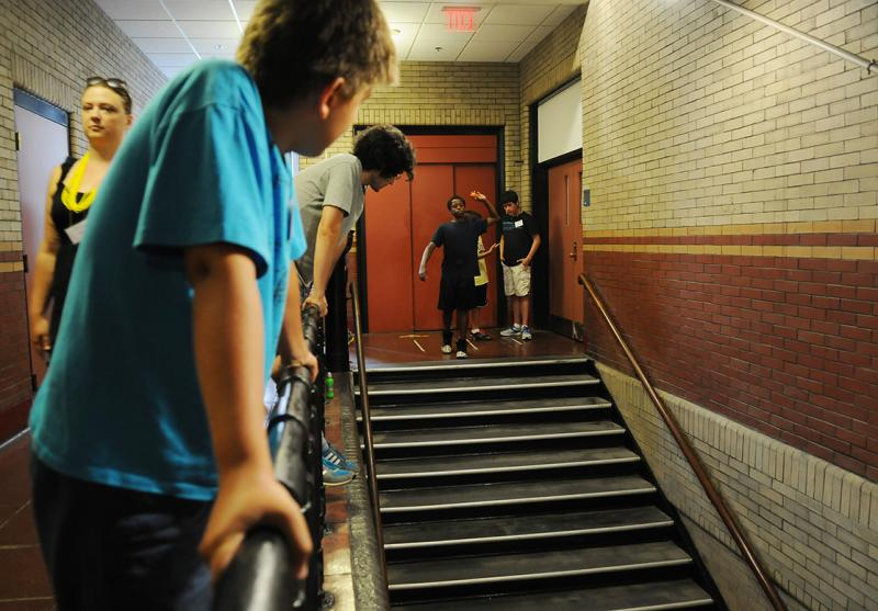A youngster tosses a ping pong ball down a flight of stairs as part of a game.