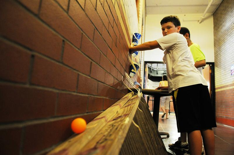 Asher Simpson, 11, tests out a game his group created called Extreme Putt Putt Ping Pong.