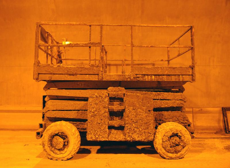 A scissor lift is covered in shotcrete, which is concrete that is shot onto walls via a hose.